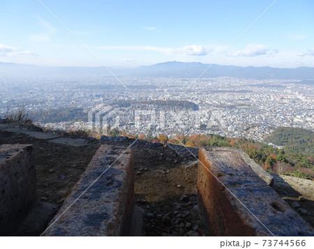 大文字山の火床とその向こうに広がる山付近に霞のかかる京都市内の景色 73744566