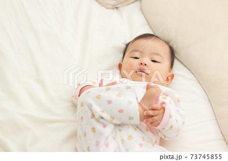 ベッドで寝転がるパジャマ姿の赤ちゃん 73745855