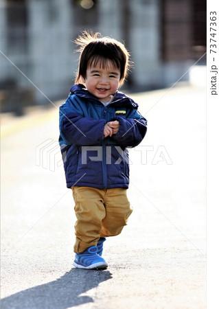 晴れた日に笑顔で散歩する2歳の男の子 73747363