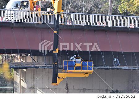 橋の補修工事 橋梁点検車で作業床を組み立てる鳶職の工事風景 73755652
