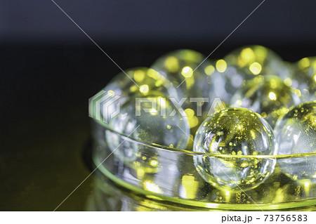 黒を背景に透明な皿の中に入った黄色に染まったガラス球 73756583