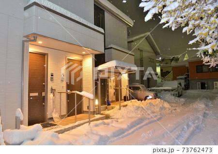 埼玉県入間市の住宅街に雪が積もり、雪かきスコップが置かれた夜景 73762473