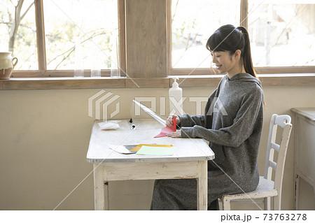 窓際のテーブルで折り紙をする女性 73763278