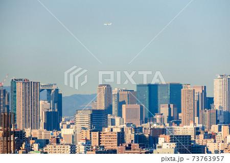 日本一の超高層ビル群、梅田方面の都市景観とその上を飛ぶ飛行機 73763957