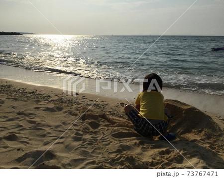 夕暮れのビーチで砂遊びをする男の子 73767471