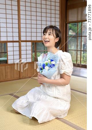 畳の上で青い薔薇の花束を抱えた可愛らしい女性 73771896