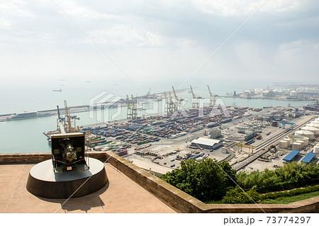 丘の上のモンジュイック城から見下ろすバルセロナの港 数々のコンテナとクレーンとコンビナートと城の大砲 73774297