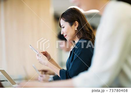 コワーキングスペースでスマホを使う女性 73780408
