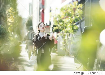 スマホで行き先を探す若い女性 73785569