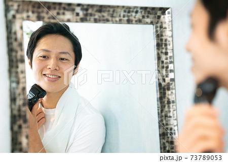 鏡を見ながらシェーバーでヒゲを剃る男性 73789053