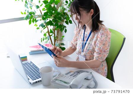 タブレットで仕事をするワンピースを着た若い女性 73791470