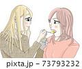 「あーん」とデザートをスプーンで食べさせる若い女性 73793232