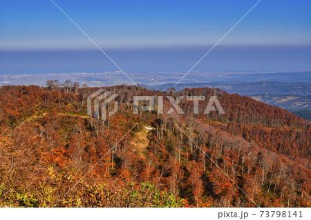 牧峠から見渡せる晴れ渡る秋空と木々の紅葉 73798141