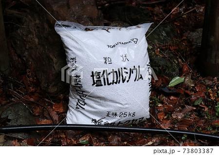 道端に置かれた凍結防止剤の塩化カルシウム 73803387