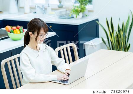 ダイニングテーブルでノートパソコンを使うメガネの女性 73820973