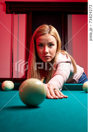 caucasian woman playing snooker, she is aiming to shoot the snooker ball 73824272
