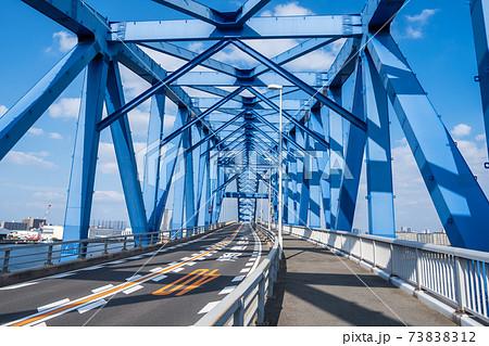 青い橋の内側から見た、頑丈な鉄のトラスと伸びるていく道路の風景 73838312