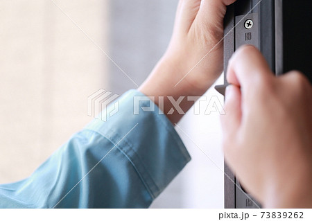 玄関ドアをメンテナンスする修理業者の男性 73839262