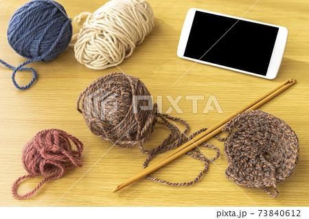 スマートフォンを見て編み物をするイメージ 73840612
