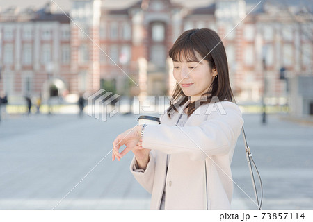 東京駅でコーヒーを持って歩く女性 73857114