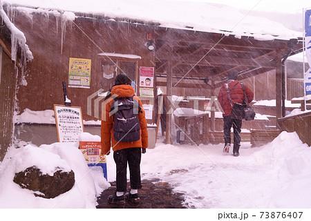 大雪の西の河原露天風呂入り口で佇むカップル 73876407