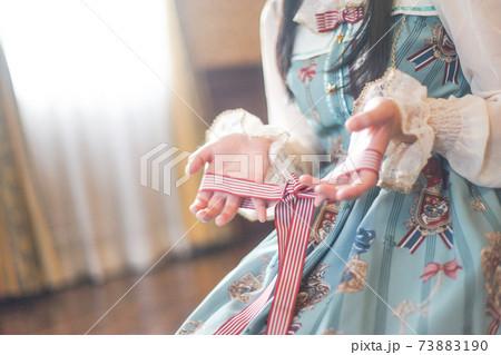 リボン遊びをするゴスロリファッションの女性 73883190