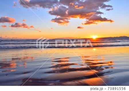 干潮で波打ち際に映り込むオレンジ色の雲 73891556