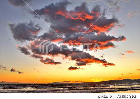 湘南海岸の夕焼けに茜色に染まるドラマチックな雲 73895892