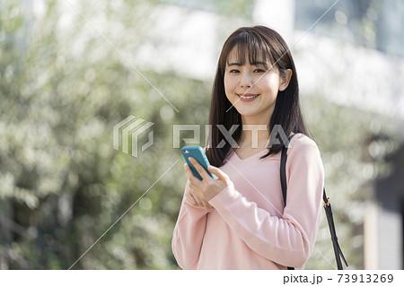 スマートフォンを持ったカメラ目線の若い女性 73913269