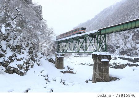 雪景色のトラス橋を走り抜ける高山本線の列車(冬の飛騨路) 73915946