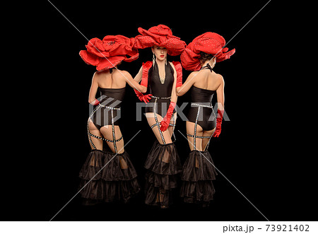 Three beautiful cabaret dancers in red hats isolated on black 73921402