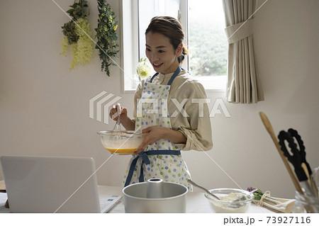 パソコンを見てお菓子作りをする女性 73927116