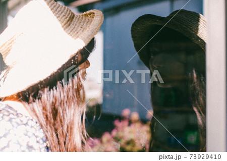 ガラスに写っている姿を見ている麦わら帽子の女性 73929410
