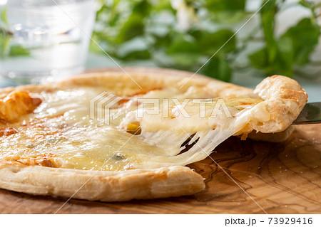 ピザサーバーで持ち上げられた、とろーりチーズのピザ 73929416