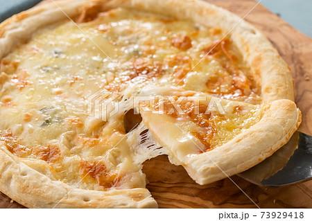 ピザサーバーで持ち上げられた、とろーりチーズのピザ 73929418