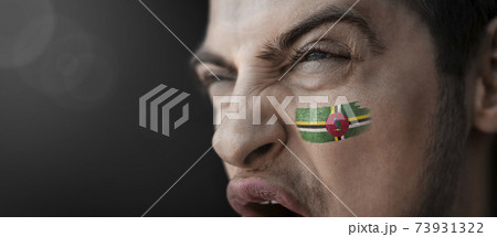 A screaming man with the image of the Dominica national flag on his face 73931322