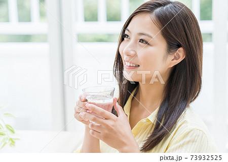 部屋で水を飲む若い女性 73932525