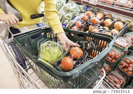 スーパーで買い物かごにトマトを入れる女性買い物客手元 73933513