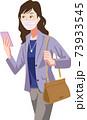 マスクをしてスマホで場所を確認して営業先へ向かう女性 73933545