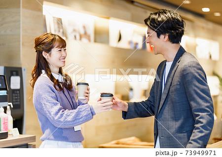 オフィスでコーヒー片手に談笑するビジネスマン 73949971