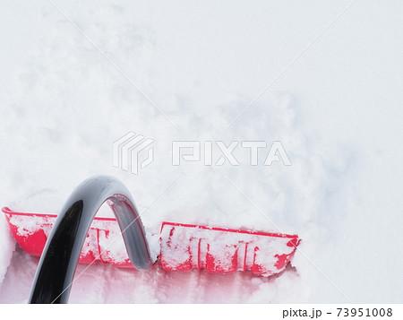 雪かきをする為に雪面へ突き刺したスコップ 73951008
