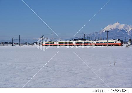 冬の岩木山をバックに快走する特急つがる号 73987880