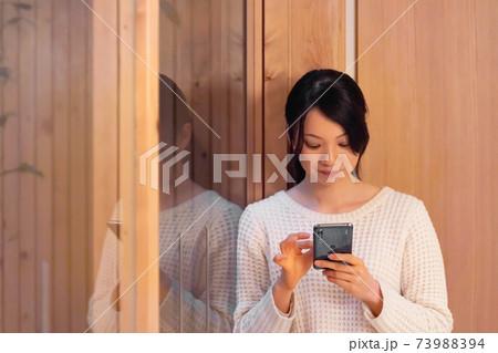 スマートフォンを操作する若い女性 73988394