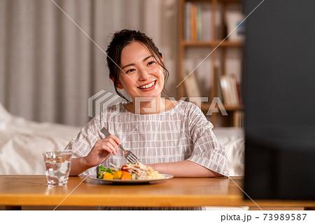 夜の食事しながらテレビを見る若い女性 73989587
