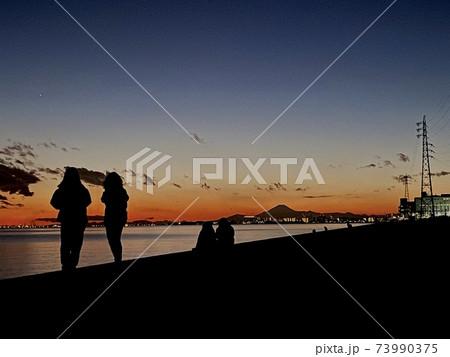 海の見える夕闇に戯れる人々のシルエット 73990375