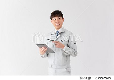 白バックのタブレットを見ながら話をする若い作業員 73992989