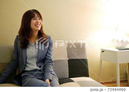 スーツを着て斜め上を笑顔で見ている20代女性 73994060