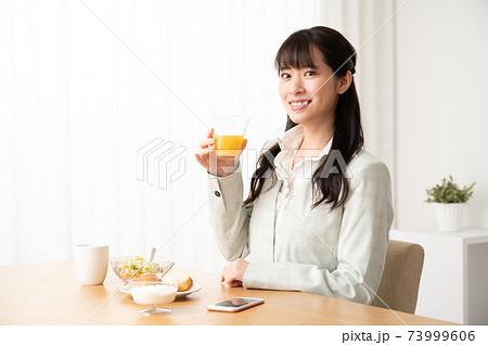 出勤前に朝食でオレンジジュースを飲む女性 73999606