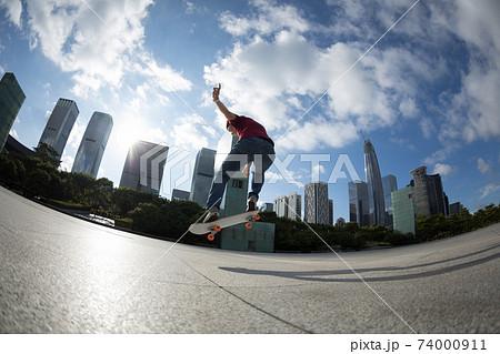 Asian woman skateboarder skateboarding in modern city 74000911