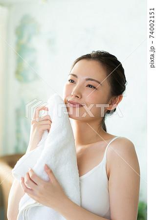 タオルで顔をふく綺麗な女性 74002151